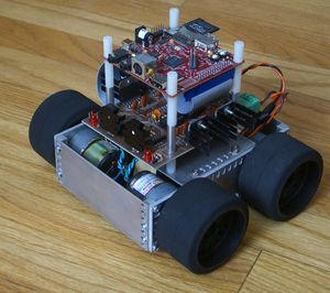 """A four-wheeled robot composed of bolted-together aluminum plates with wide black tires protruding from either side.  On top, two circuit boards are mounted with standoffs, the smaller BeagleBoard on top."""